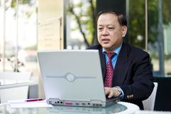 Hogere Aziatische zakenman die laptop PC met behulp van royalty-vrije stock afbeeldingen