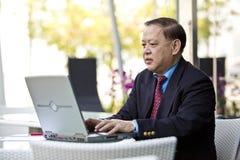 Hogere Aziatische zakenman die laptop PC met behulp van stock foto's