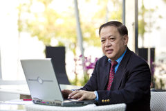 Hogere Aziatische zakenman die laptop PC met behulp van stock afbeeldingen