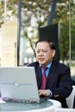 Hogere Aziatische zakenman die laptop PC met behulp van royalty-vrije stock afbeelding