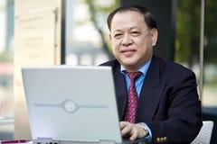 Hogere Aziatische zakenman die laptop PC met behulp van stock fotografie