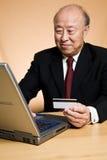 Hogere Aziatische zakenman die online winkelt Royalty-vrije Stock Afbeeldingen