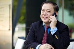 Hogere Aziatische zakenman die slimme telefoon met behulp van stock afbeelding