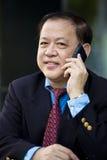Hogere Aziatische zakenman die slimme telefoon met behulp van stock foto