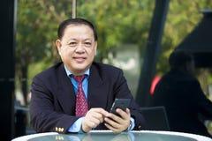 Hogere Aziatische zakenman die slimme telefoon met behulp van stock foto's