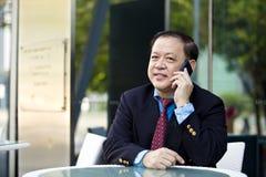 Hogere Aziatische zakenman die slimme telefoon met behulp van royalty-vrije stock afbeelding