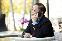 Hogere Aziatische zakenman die slimme telefoon met behulp van royalty-vrije stock afbeeldingen