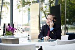 Hogere Aziatische zakenman die slimme telefoon met behulp van royalty-vrije stock foto's
