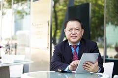 Hogere Aziatische zakenman die tabletpc met behulp van royalty-vrije stock foto