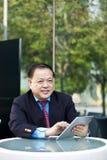 Hogere Aziatische zakenman die tabletpc met behulp van stock afbeeldingen