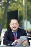 Hogere Aziatische zakenman die tabletpc met behulp van royalty-vrije stock afbeelding