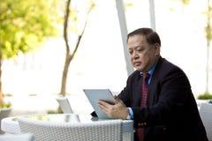 Hogere Aziatische zakenman die tabletpc met behulp van royalty-vrije stock afbeeldingen