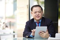 Hogere Aziatische zakenman die tabletpc met behulp van stock foto