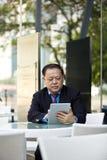 Hogere Aziatische zakenman die tabletpc met behulp van royalty-vrije stock foto's