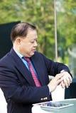 Hogere Aziatische zakenman die tijd bekijken stock afbeelding