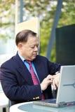 Hogere Aziatische zakenman die tijd bekijken stock foto