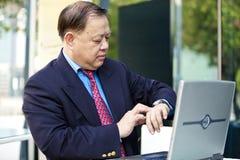 Hogere Aziatische zakenman die tijd bekijken royalty-vrije stock afbeeldingen