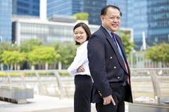 Hogere Aziatische zakenman en jong vrouwelijk Aziatisch uitvoerend het glimlachen portret royalty-vrije stock afbeelding