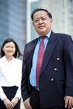 Hogere Aziatische zakenman en jong vrouwelijk Aziatisch uitvoerend het glimlachen portret royalty-vrije stock afbeeldingen