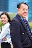 Hogere Aziatische zakenman en jong vrouwelijk Aziatisch uitvoerend het glimlachen portret royalty-vrije stock foto's
