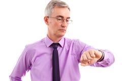 Hogere bedrijfsmens die aan geïsoleerd horloge kijken Stock Fotografie