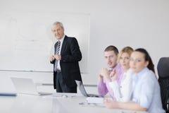 Hogere bedrijfsmens die een presentatie geeft Stock Foto
