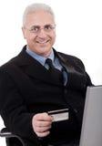 Hogere bedrijfsmens die online aankoop maakt Stock Foto's