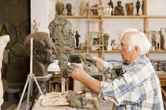 Hogere beeldhouwer die beeldhouwwerk maakt sideview Royalty-vrije Stock Foto's