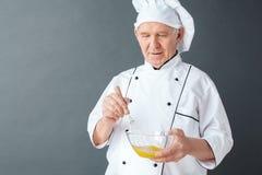 Hogere chef-kokstudio die zich op grijs het mengen zich blij eierenclose-up bevinden royalty-vrije stock foto