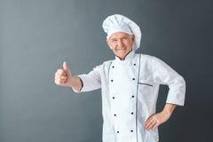 Hogere chef-kokstudio status geïsoleerd op grijze tonende duim die omhoog vriendschappelijke camera kijken royalty-vrije stock afbeelding