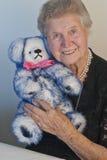 Hogere dame die in de haar jaren '80 teddybeer knuffelt Royalty-vrije Stock Afbeelding