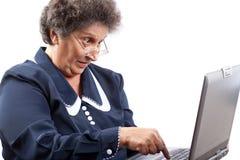 Hogere dame die laptop met behulp van Stock Foto