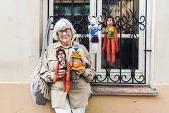 Hogere dame die met de hand gemaakt gebreid speelgoed op de straat verkopen stock afbeeldingen