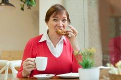 Hogere dame die ontbijt in koffie hebben Royalty-vrije Stock Afbeeldingen