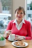 Hogere dame die ontbijt in koffie hebben Royalty-vrije Stock Afbeelding