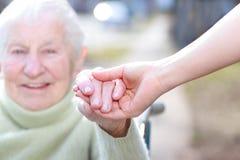 Hogere Dame en de Jonge Handen van de Holding van de Vrouw stock afbeelding