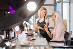 Hogere dame en haar make-upkunstenaar die nieuwe oogschaduwwen bespreken stock fotografie