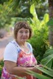 Hogere dame met haar installaties in de tropische tuin Stock Foto's