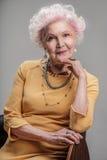Hogere dame met heldere make-upzitting op stoel royalty-vrije stock fotografie