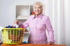 Hogere dame tijdens het vouwen van wasserij stock afbeelding