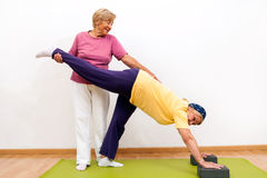 Hogere dames die elkaar met het uitrekken van oefening helpen Stock Afbeelding