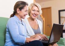 Hogere dames met laptop stock foto