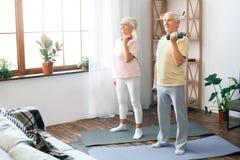 Hogere de gezondheidszorglift van de paaroefening samen thuis op domoren Stock Afbeeldingen