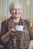 Hogere de koffie van de vrouwenholding mok en het glimlachen stock fotografie