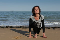 Hogere de zonbegroeting van de vrouwenyoga op het strand Royalty-vrije Stock Fotografie