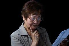 Hogere die vrouw door haar financiële rekeningen op zwarte backgroun wordt verrast royalty-vrije stock afbeelding