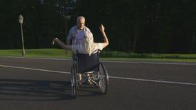 Hogere echtgenoot spinnende vrouw op rolstoel in park stock footage