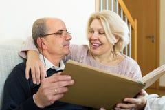 Hogere echtgenoten met beeldalbum binnen Stock Fotografie