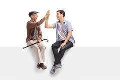 Hogere en jonge kerel op een paneel hoog-fiving elkaar Stock Fotografie