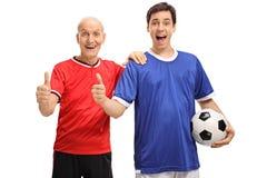 Hogere en jonge mens die een voetbal houden en duim maken omhoog ondertekenen Stock Fotografie